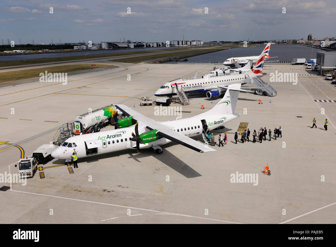 passengers with carry-on bags boarding an Aer Arann ATR 72-200 with Air BP refuelling bowser, British Airways BA CityFlyer Embraer 190, Scot Airways D - Stock Image