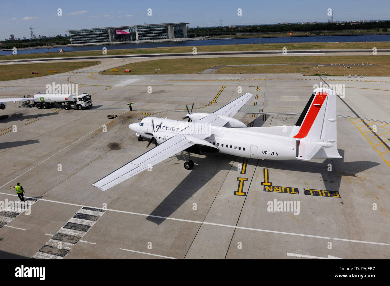 marshaller with bats controlling CityJet Fokker F-50 taxiing at London City with refuelling bowser behind - Stock Image