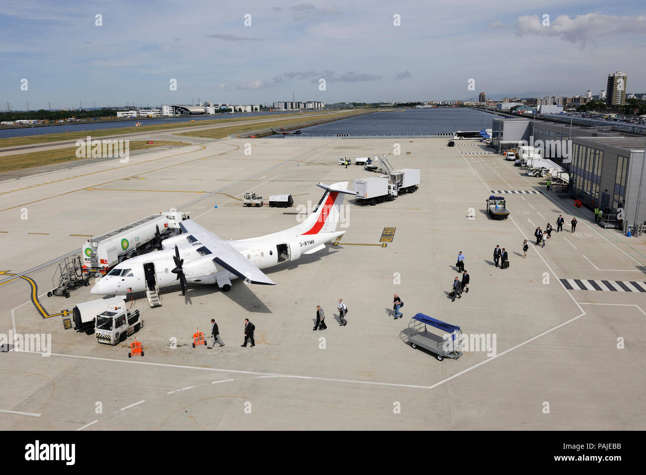 passengers with carry-on bags boarding a Scot Airways Dornier Do-328-100, tractor, Houchin ground power unit, Air BP refuelling bowser, baggage trolle - Stock Image