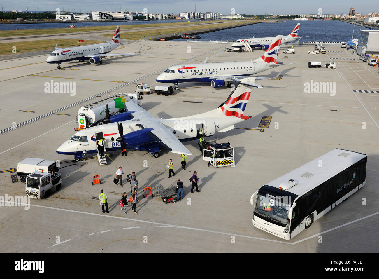 Air BP refuelling bowser, passengers collecting bags from trolley, British Airways - Sun Air Dornier Do-328-100 with British Airways BA CityFlyer Embr - Stock Image