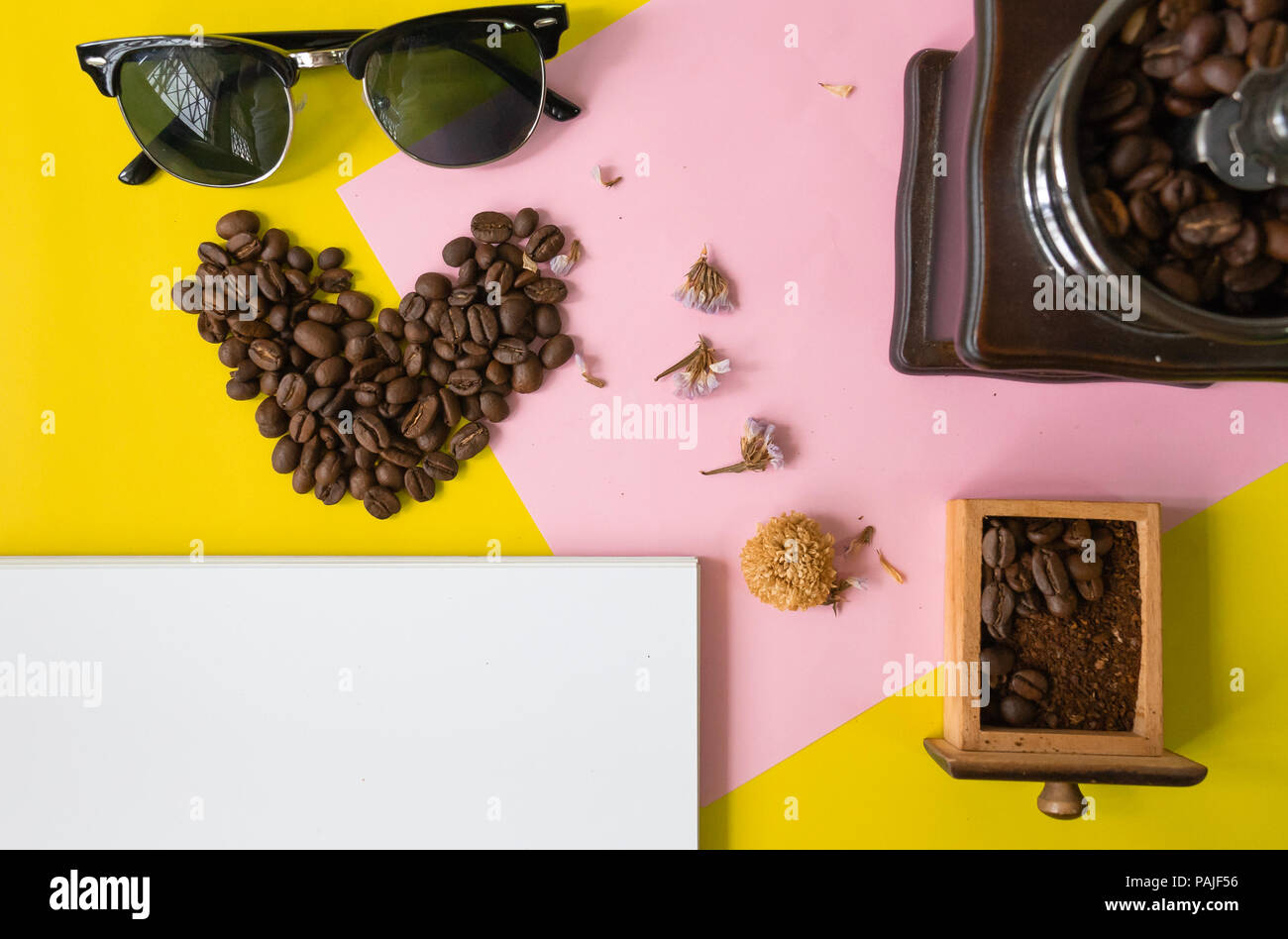 top view flat layer heart smile  icon shape ,sun glasses, vintage wooden coffee grinder and blank book for copy space  on two tone multicoloured  back - Stock Image