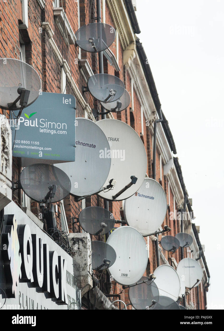 A mass of satellite dishes on the exterior walls of flats above shops in Green Lanes, Haringey, north London, UK - Stock Image