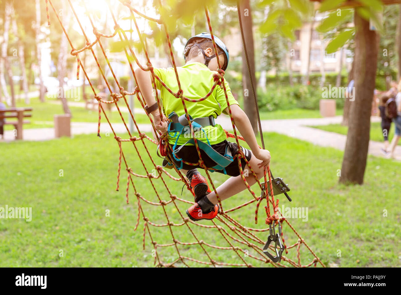 Little boy in safety equipment climbing on rope wall at adventure park. Children summer sport extreme outdoor activity. Back view. - Stock Image