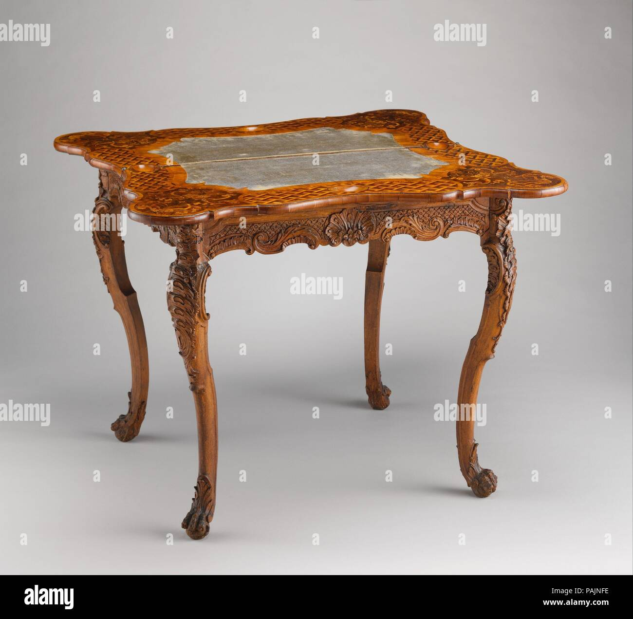 Card table. Culture: German, Bamberg. Dimensions: closed: 29 1/2 × 37 1/2 × 18 1/2 in. (74.9 × 95.3 × 47 cm). Date: ca. 1745-50.  According to the Bamberg city archives, Nicolaus Bauer (active 1758-1771) made gaming tables for Seehof Castle, the summer residence of the bishops of Würzburg and Bamberg, during the 1750s and 60s. This example, coming from Seehof, can be included in his output. The folding top exhibits marquetry motifs typical of German workshops, while carved asymmetrical shellwork elements adorn the knees. Museum: Metropolitan Museum of Art, New York, USA. - Stock Image