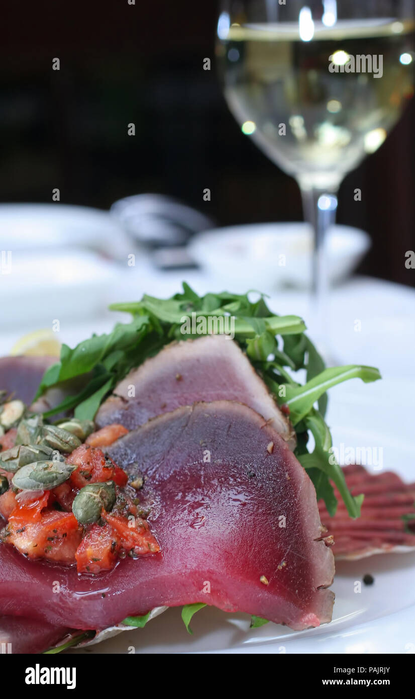Slices of bluefin tuna served in restaurant with pumpkin seeds, tomato, raw rocket and white wine - macro side view - Stock Image
