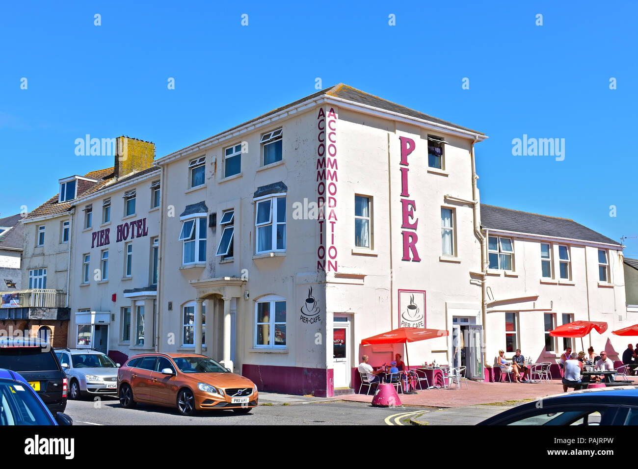 People enjoying a drink outside the Pier Hotel, which is situated on the Eastern Esplanade overlooking the sea at Porthcawl, South Wales - Stock Image