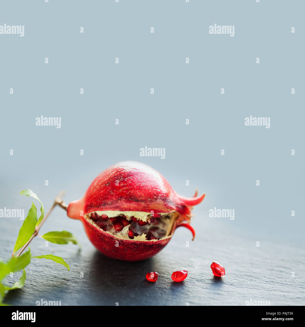 Ripe red fruit pomegranate with seeds on black stone and gray background. close-up photo. copy space - Stock Image