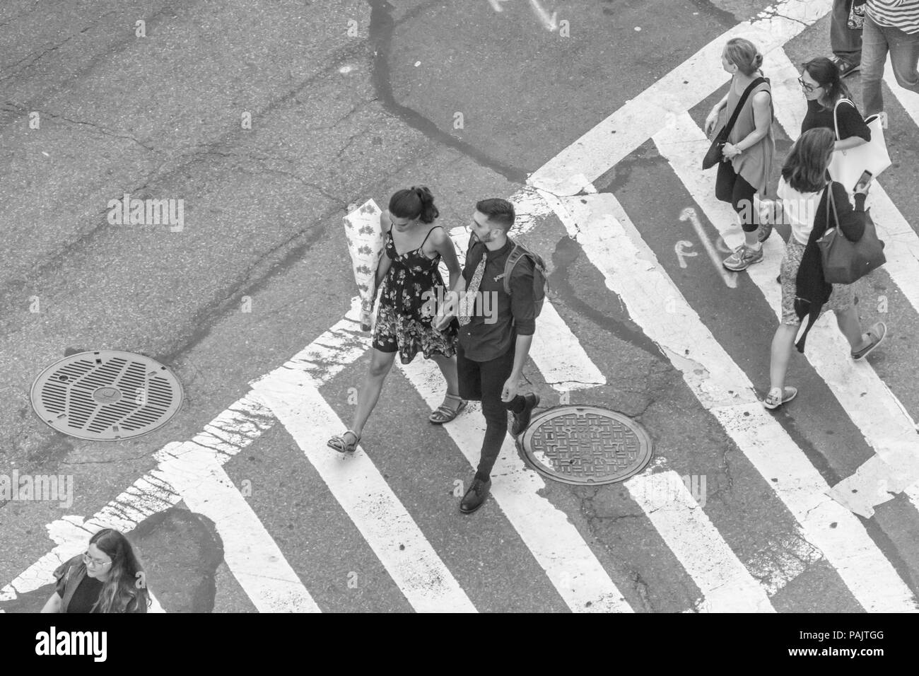 a view from above of people walking in a crosswalk at 61st street and Broadway in New York City - Stock Image