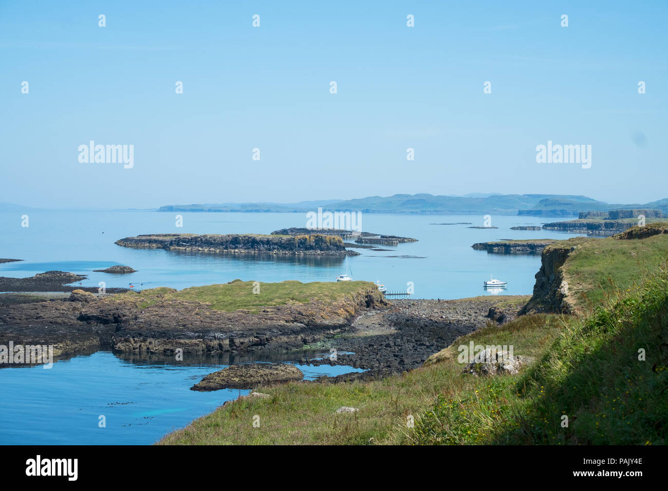Harbour on Lunga, Treshnish Isles, from the clifftop. Small boats can be seen at anchor. Stock Photo