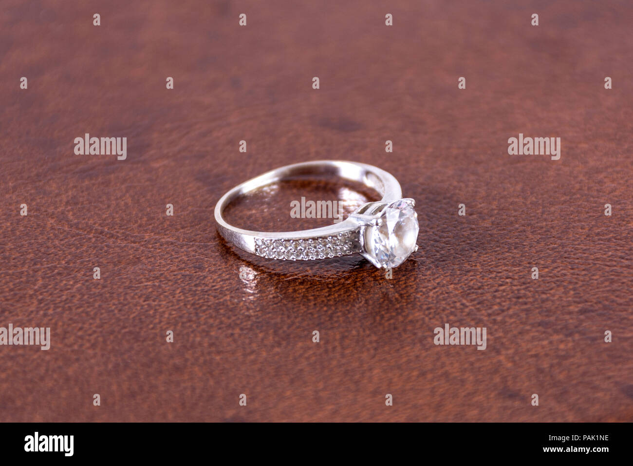 Diamond Silver Engagement Wedding Ring On Leather Brown Blurred And