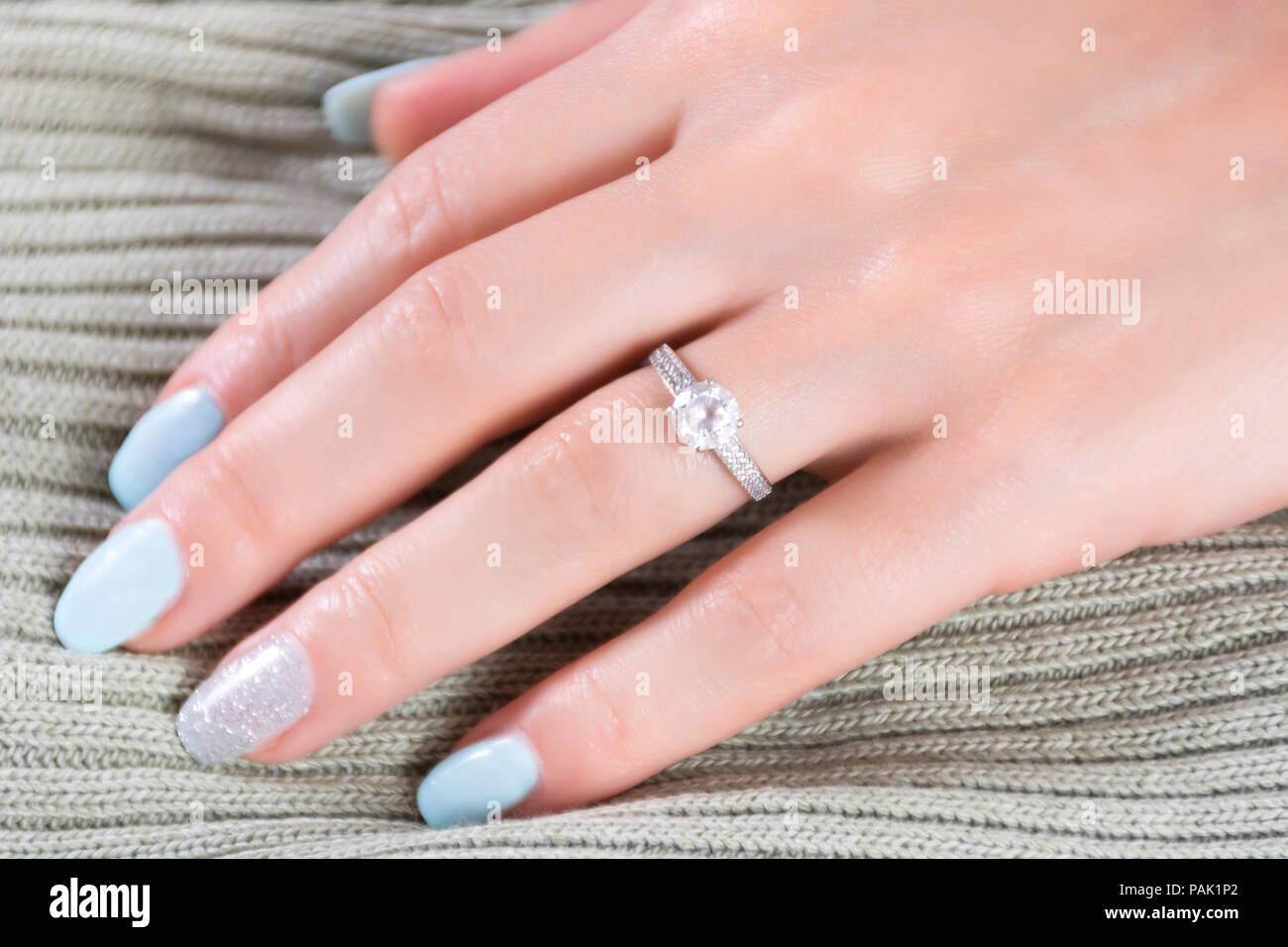 Diamonds wedding engagement rings on female finger with blue nails ...