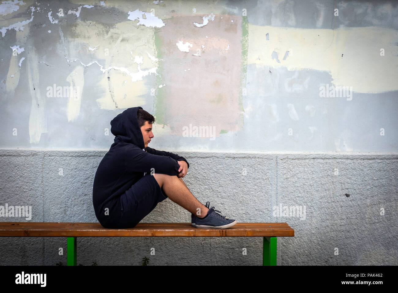 little boy sad sitting alone at school hides his face stock photo