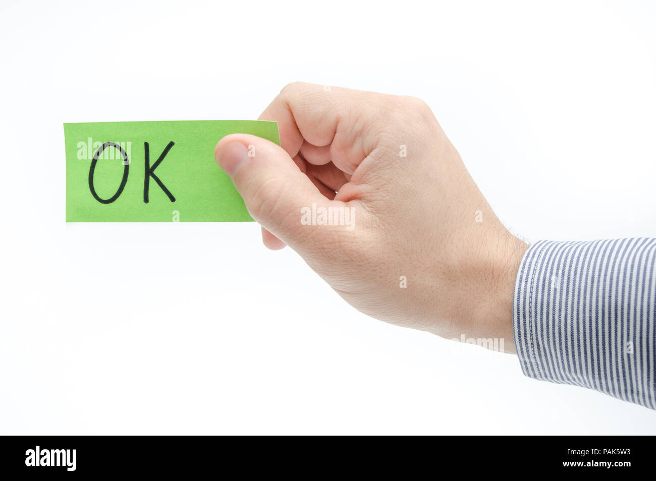 OK approval concept suggested by a green ticket in a business man's hand on a white background - Stock Image