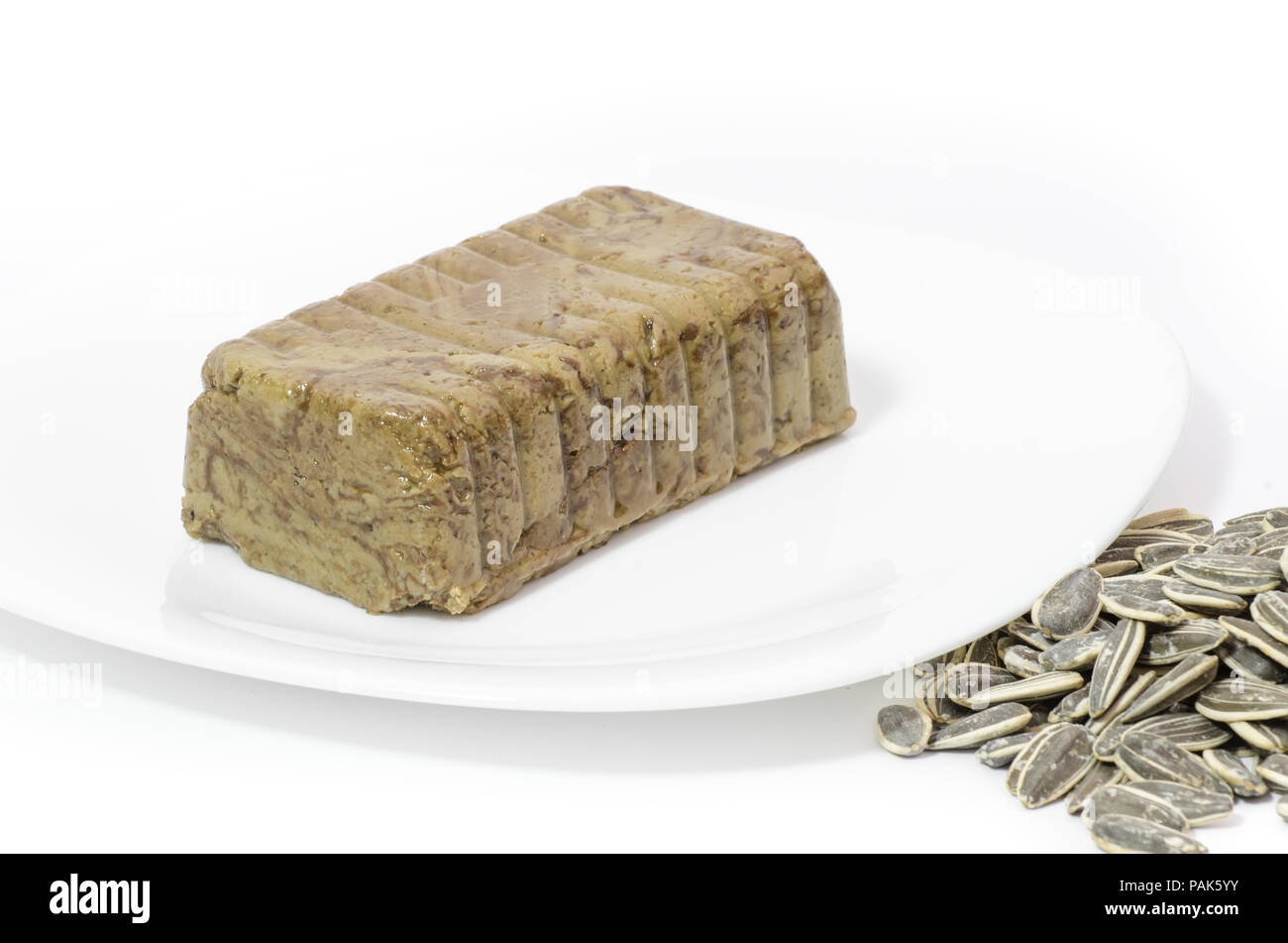 Traditional eastern europe dessert called halva made from sunflower seeds and cocoa on a white background - Stock Image