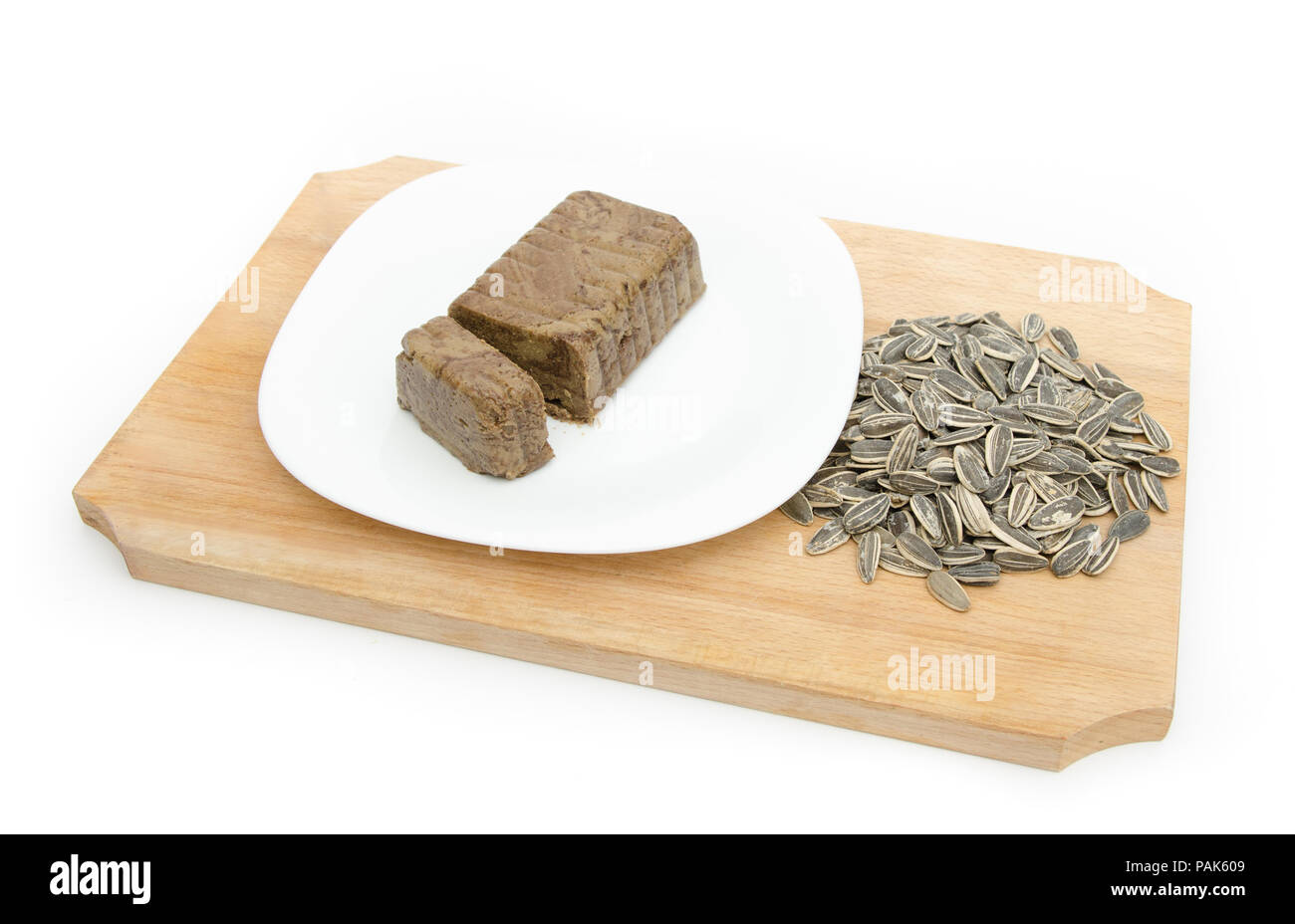 Halva or halvah traditional orietnal and eastern europe dessert made from sunflower seeds and cocoa on a white plate on a wood cutiing board on a whit - Stock Image