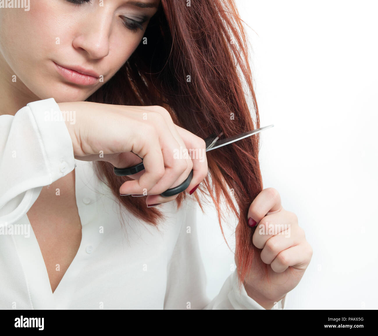 Beautiful redhead young woman cutting her hair with a pair of scissors on a white isolated background suggesting a new hair style or hair problems reg