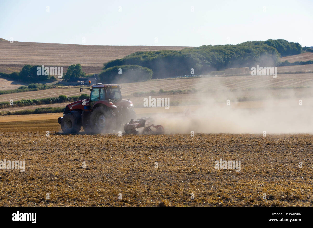 Came Down, Dorchester, Dorset, UK.  23rd July 2018. UK Weather.  A farmer with a tractor cultivating a field throws up plumes of dust from the parched land at Came Down near Dorchester in Dorset as the heatwave and drought continues.  Picture Credit: Graham Hunt/Alamy Live News - Stock Image