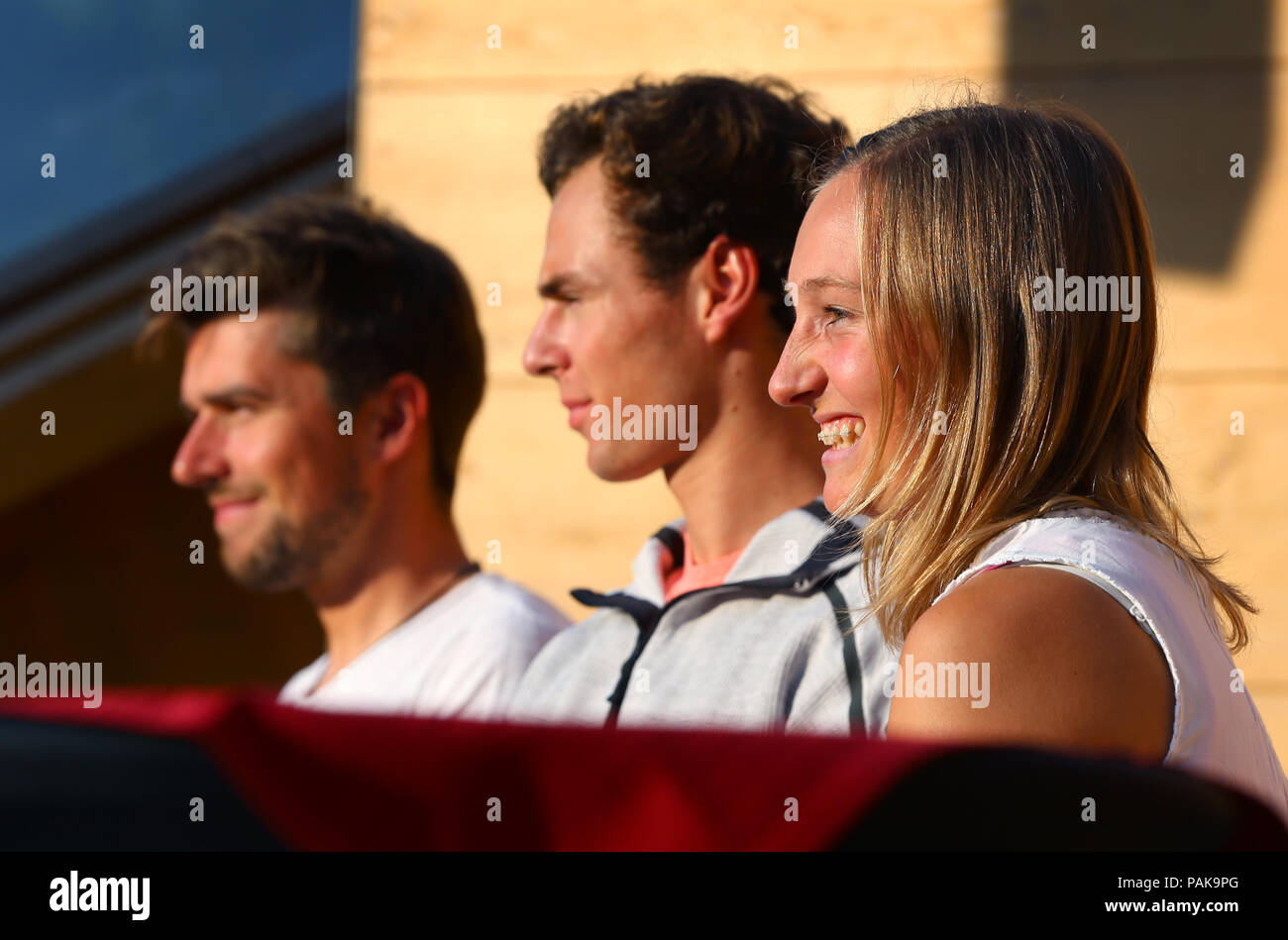 Germany, Oberstdorf. 23rd July, 2018. The Nordic combined athletes Johannes Rydzek (l-r), Vinzenz Geiger and the ski jumper Katharina Althaus sit on the podium in front of the logo presentation for the FIS Nordic World Ski Championships 2021. Credit: Karl-Josef Hildenbrand/dpa/Alamy Live News - Stock Image