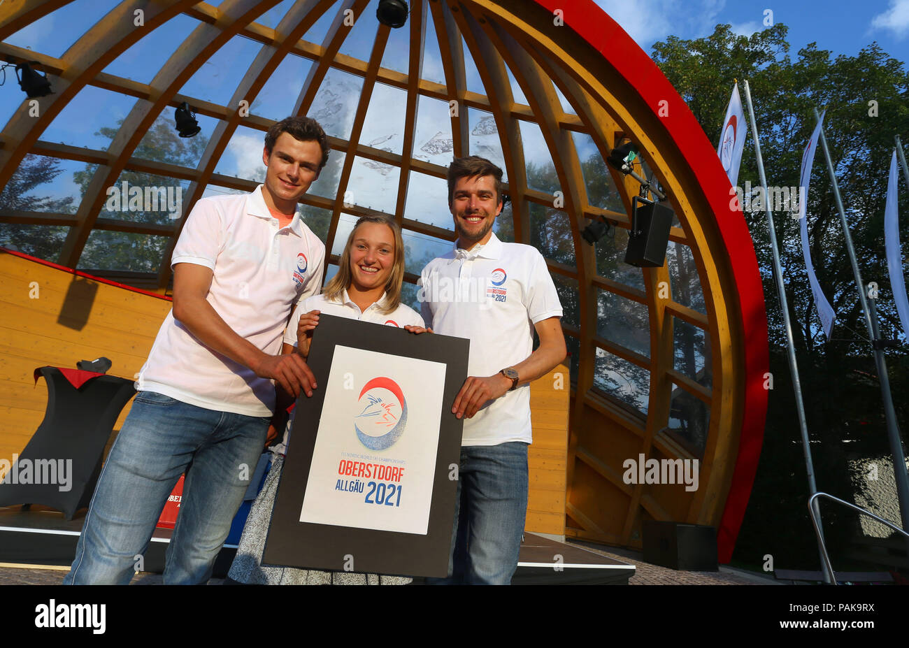 Oberstdorf, Germany. 23rd July, 2018. 23.07.2018, Bayern, Oberstdorf: The Nordic combined athletes Johannes Rydzek (r), Vinzenz Geiger (l) and ski jumper Katharina Althaus (M) present the logo for the FIS Nordic World Ski Championships 2021 on the podium. Credit: Karl-Josef Hildenbrand/dpa/Alamy Live News - Stock Image