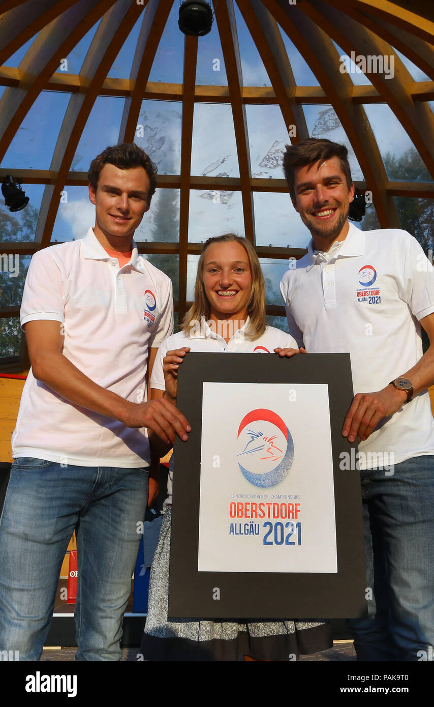 Germany, Oberstdorf. 23rd July, 2018. The Nordic combined athletes Johannes Rydzek (r), Vinzenz Geiger (l) and ski jumper Katharina Althaus (M) present the logo for the FIS Nordic World Ski Championships 2021 on the podium. Credit: Karl-Josef Hildenbrand/dpa/Alamy Live News - Stock Image