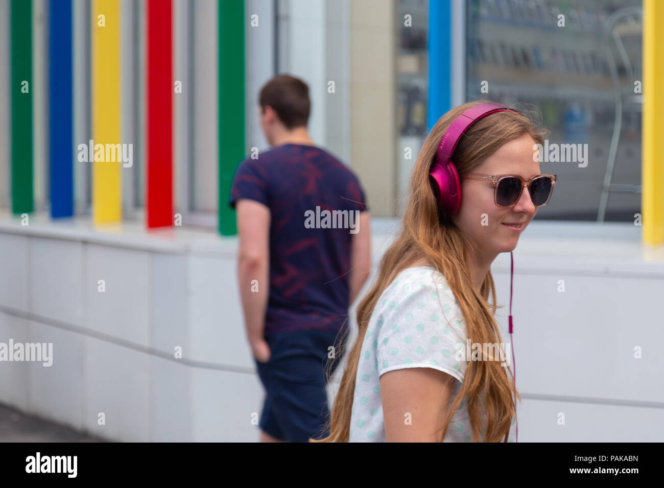 Moscow, Russia. 22nd July 2018. A group of young people in identical multi-colored headphones SONY 'h.ear on' gathered for party near the entrance to the metro station Savelovskaya. After a couple of minutes the audience began to applaud and with smiles on their faces quickly dissolved in the crowd of passengers. Remote Moscow is a performance-journey across Moscow for a group of 50 people. This is a theatrical project of a new format in genre of 'promenade-performance', combines elements of a performance, an excursion, a computer game and a quest. Credit: Andrey Yanevich/Alamy Live News - Stock Image