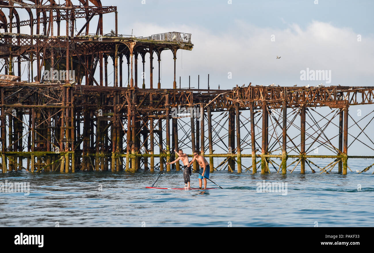 Brighton UK 24th July 2018 - Paddle boarders pass by the West Pier early this morning as the heatwave conditions continue throughout some parts of Britain with an amber warning being issued and people being advised to stay out of the sun during the hottest parts of the day Credit: Simon Dack/Alamy Live News - Stock Image