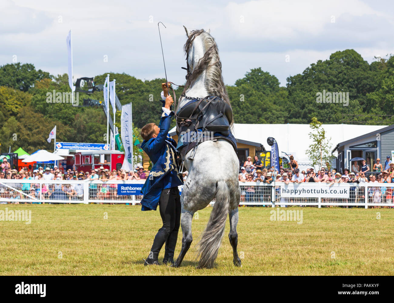 Brockenhurst, Hampshire, UK. 24th July 2018. Crowds flock to the first day of the New Forest & Hampshire County Show on a hot sunny day. The Atkinson Stunt Display team who appeared on Poldark and Peaky Blinders thrill the crowds with their tricks and stunts, including Roman Riding, Drags, Falls, Pick Ups, Flips, Horses Rearing and Laying Down. Credit: Carolyn Jenkins/Alamy Live News - Stock Image