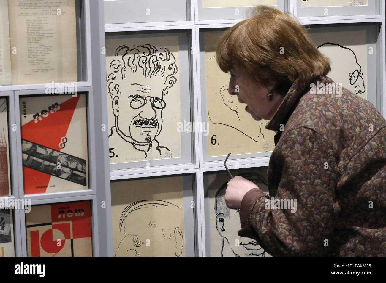 MOSCOW, RUSSIA - JULY 24, 2018: A visitor views early 1920s mocking portraits of LEF [Left Front of Arts] members on display at an exhibition titled 'Vladimir Mayakovsky - There and Over Here' and held at Moscow's Vladimir Dahl Russian State Literary Museum to mark Russian poet Vladimir Mayakovsky's 125th birthday. Sergei Savostyanov/TASS - Stock Image