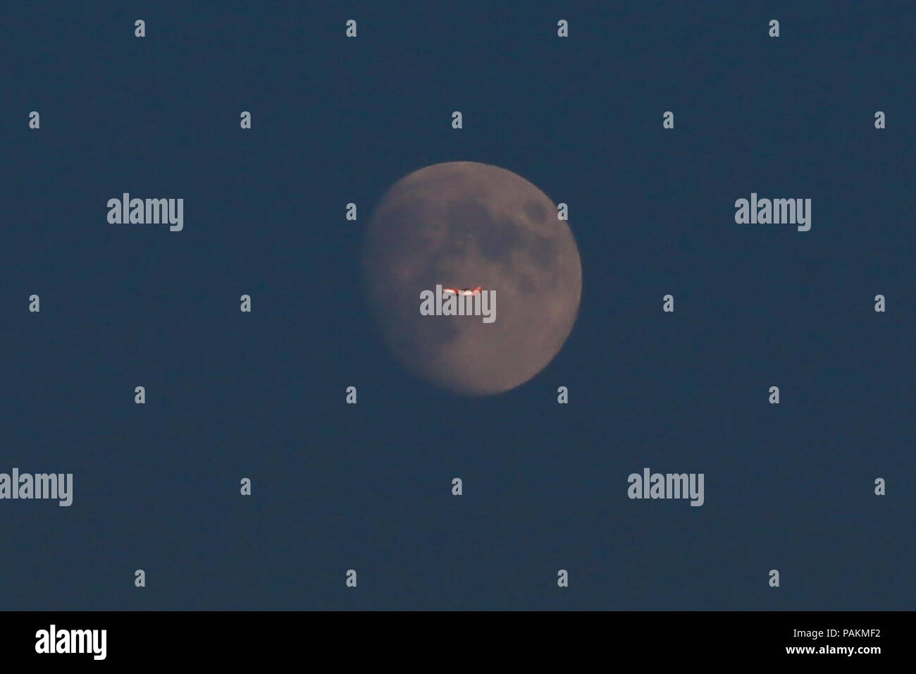 London. UK 24 July 2018 - A plane flies through a nearly full moon over north London. Total lunar eclipse will be visible in London on 27 and 28 July 2018.  Credit: Dinendra Haria/Alamy Live News Stock Photo