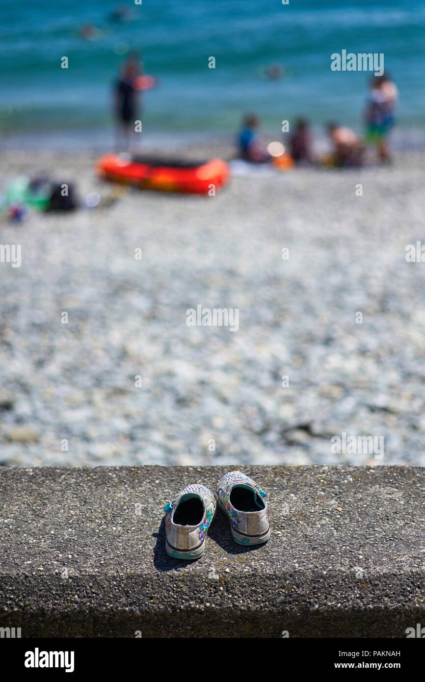 Pair of childrens shoes left behind on a sea wall at the beach - Stock Image