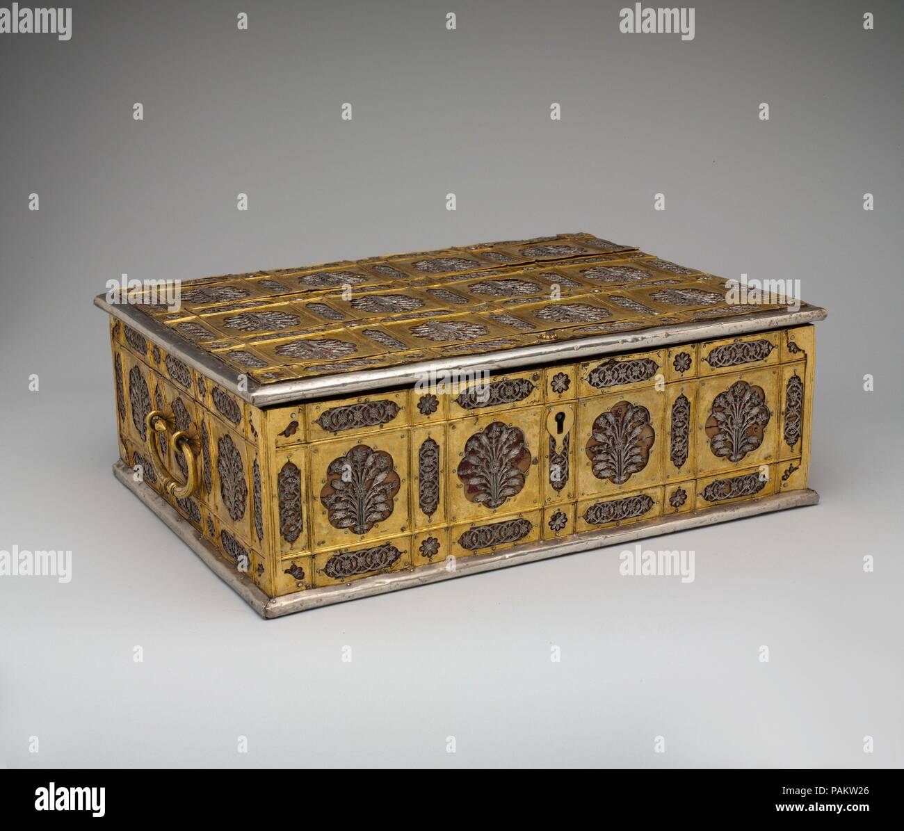 """Writing Box with Lattice and Flower Design. Dimensions: H. 5 3/8 in. (13.6 cm)   W. 16 3/8 in. (41.5 cm)  Depth 12 5/8 in. (32 cm). Date: mid-17th century.  The gilded copper sheets and silver plaques covering the exterior of this box are fashioned in a classic """"lattice and flower"""" variant of the flower style. Because of the technique of fastening the metal over the wood, the box has been attributed to Burhanpur, a city in the northern Deccan, where similar work is found in architecture. Museum: Metropolitan Museum of Art, New York, USA. Stock Photo"""
