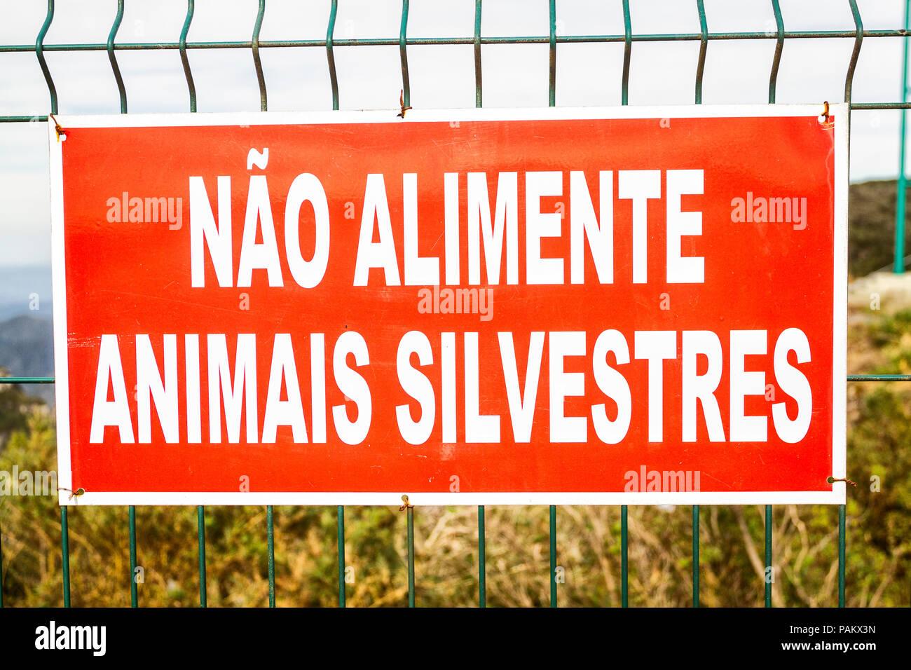 Sign written in Portuguese warning to not feed wild animals. Bom Jardim da Serra, Santa Catarina, Brazil. - Stock Image