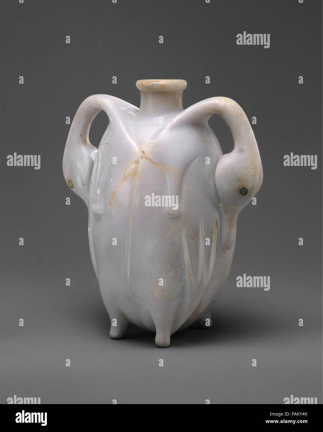Perfume Vessel in the Shape of Two Trussed Ducks. Dimensions: h. 17.4 cm (6 7/8 in); w. 15.3 cm (6 in); d. 9.2 cm (3 5/8 in). Dynasty: Dynasty 17. Date: ca. 1580-1550 B.C..  The flask - delicately carved from the rare stone material anhydrite -  has the form of a pair of  trussed ducklings placed back-to-back. Their necks arch far from the bodies and the joints of their legs make four little knuckles for the vessel to stad on. The birds' eyes are inlaid with copper. Trussed duck were a common offering to the dead.  It is, therefore, possible that this vessel, although originally without doubt  - Stock Image