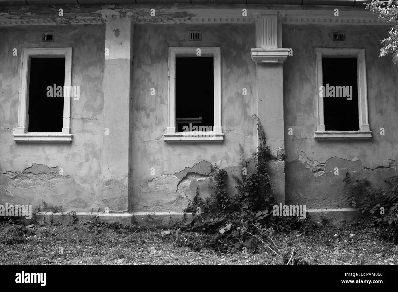 Three windows in an abandoned building in black and white - Stock Image