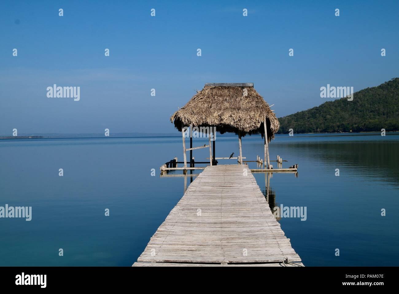 Long boardwalk on a blue lake reflecting a blue sky - Stock Image