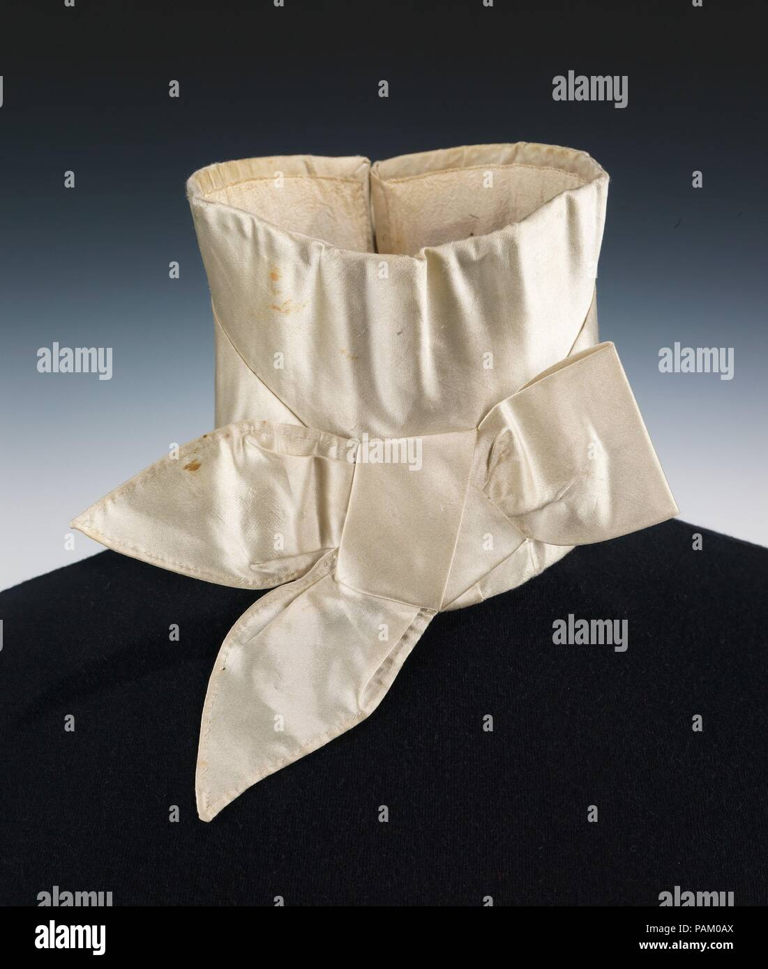 Wedding stock. Culture: American. Date: 1835.  This is an elegant example of a stock, the standard neckwear for men in the early 19th century, to be worn over the high stand collar of the shirt.  The styles of the 1830s were prescribed by fashionable dandies, such as Alfred Guillaume Gabriel, Count D'Orsay (1801-1852), a French emigrant who had relocated to England in 1829, and influenced artists and writers in wit and dress.  The crisp and complete stock with a tailored bow was essential in fashionable formal dress. Museum: Metropolitan Museum of Art, New York, USA. - Stock Image