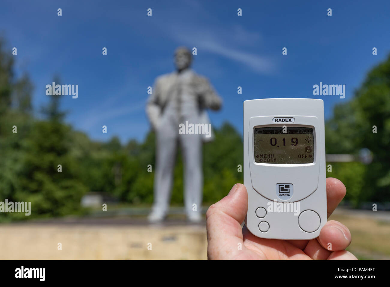 Radiation reading in the town of Chernobyl, Northern Ukraine with the statue of Lenin in the back round - Stock Image