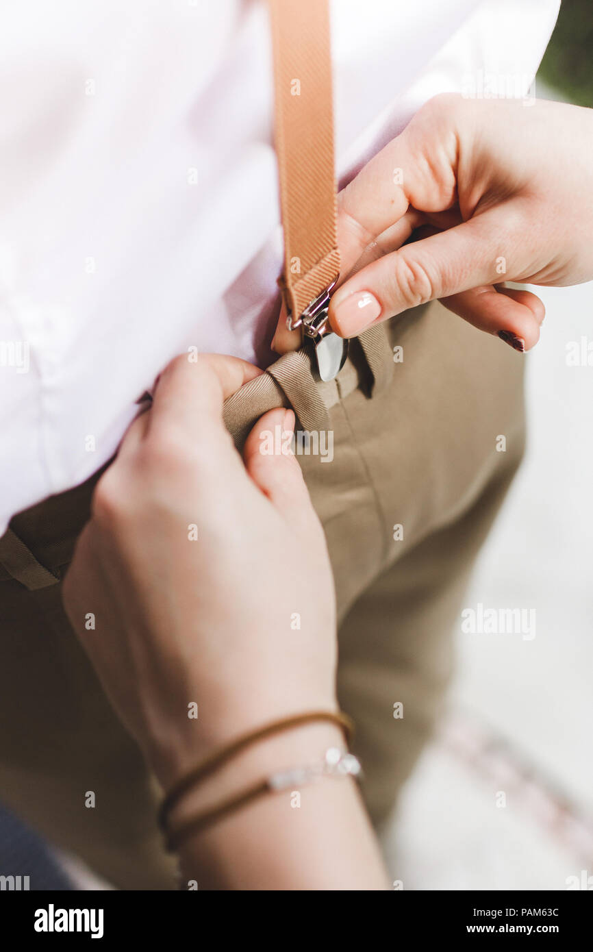 Woman hands help to wear suspenders for pants for man - Stock Image