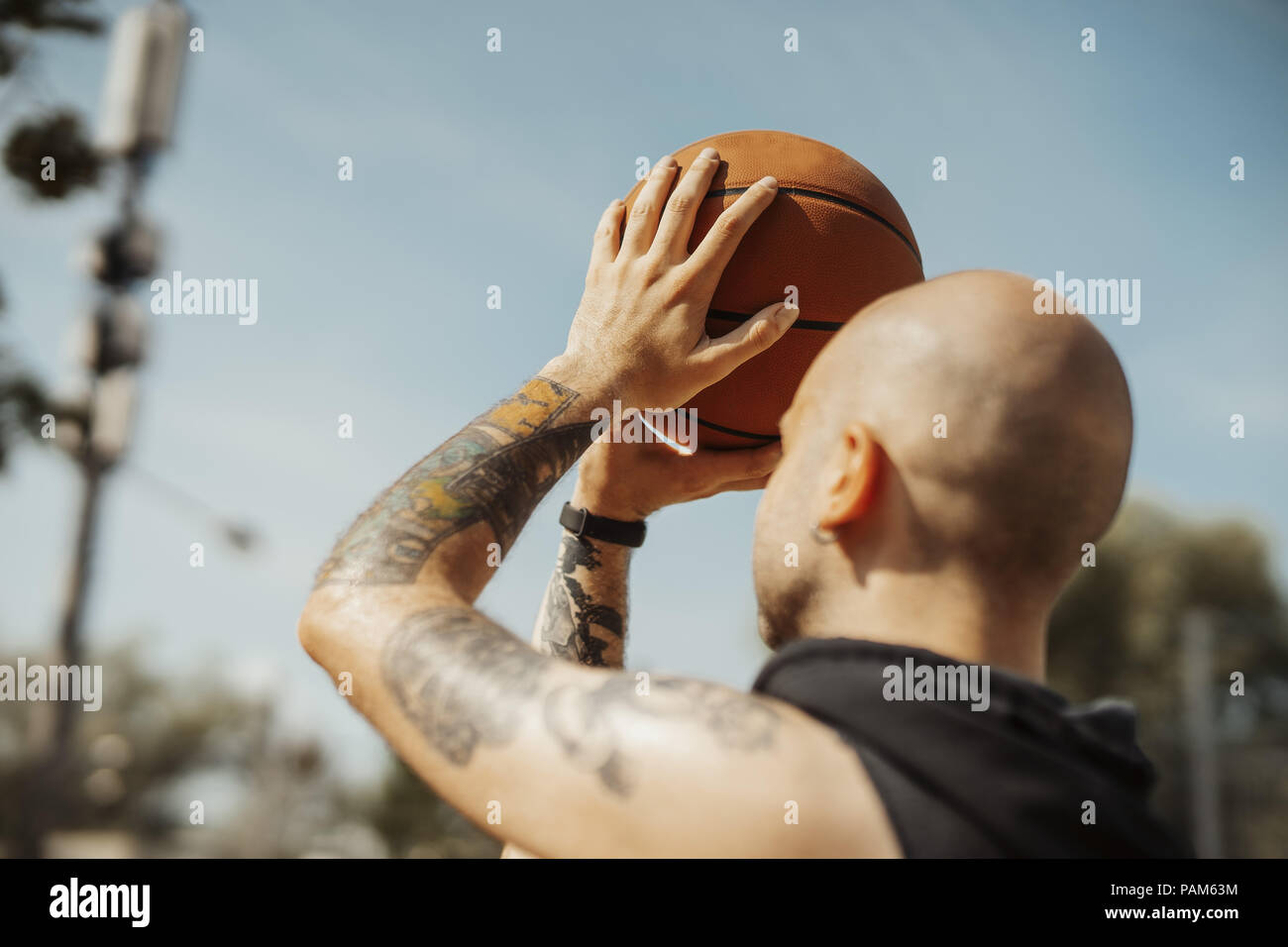 Close up of bald attractive man playing basketball on the basketball court. - Stock Image