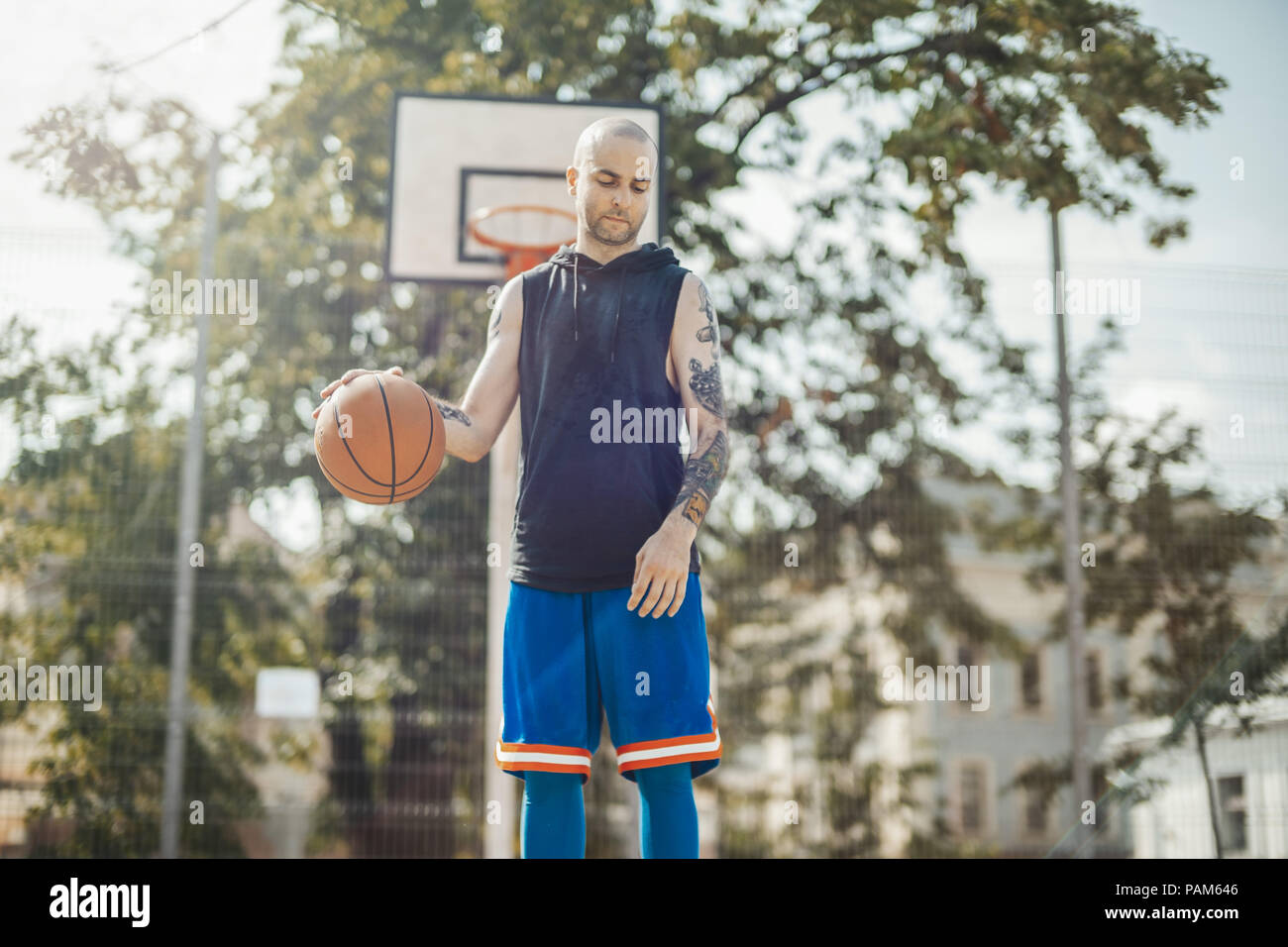 Bald attractive man playing basketball on the basketball court. Man is on focus and foreground, basketball hoop and board are on background and blurre - Stock Image