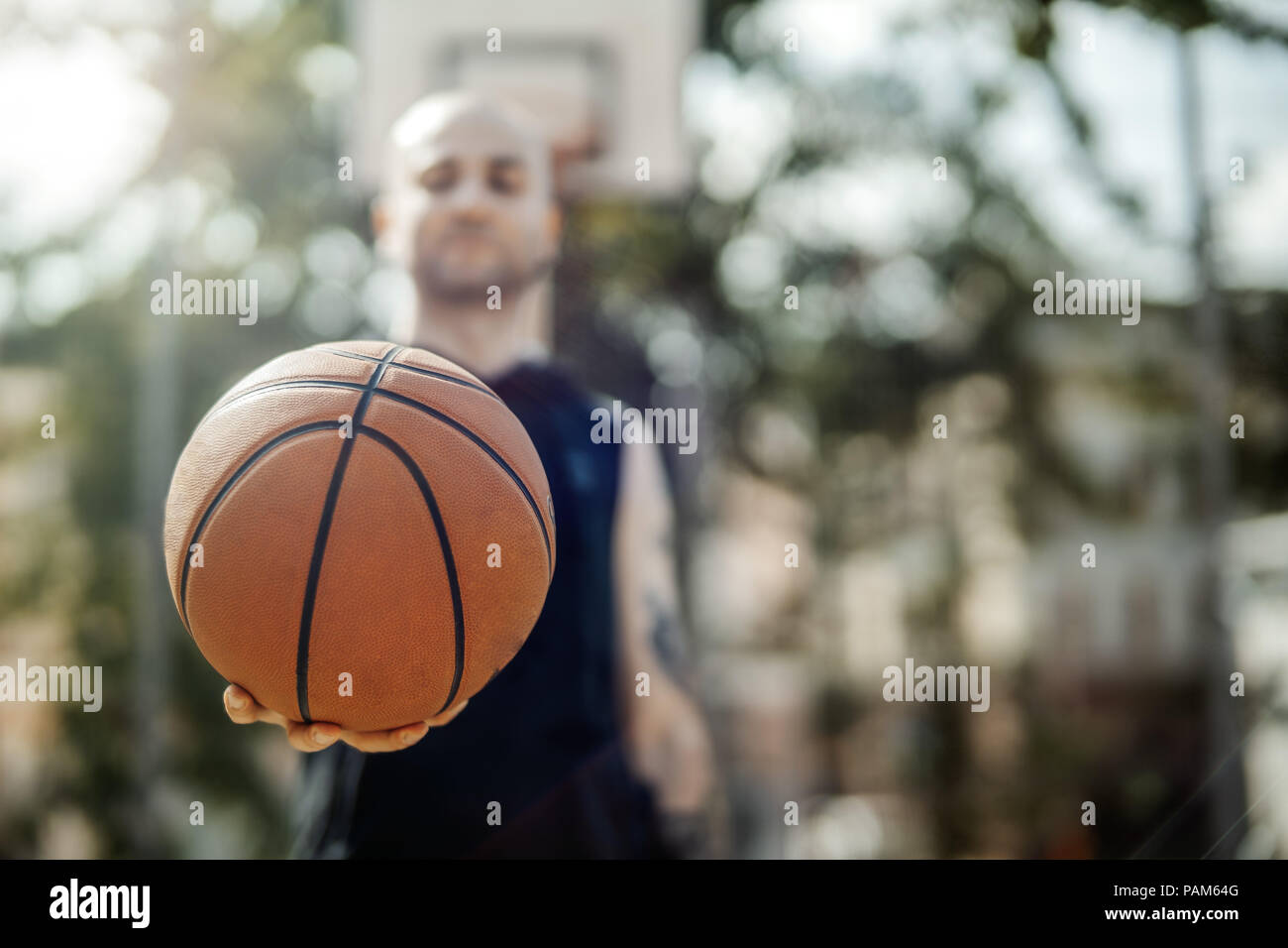 Close up of bald attractive man holding basket ball. Ball is on focus and foreground. Man, basketball hoop and board are on background and blurred. Stock Photo