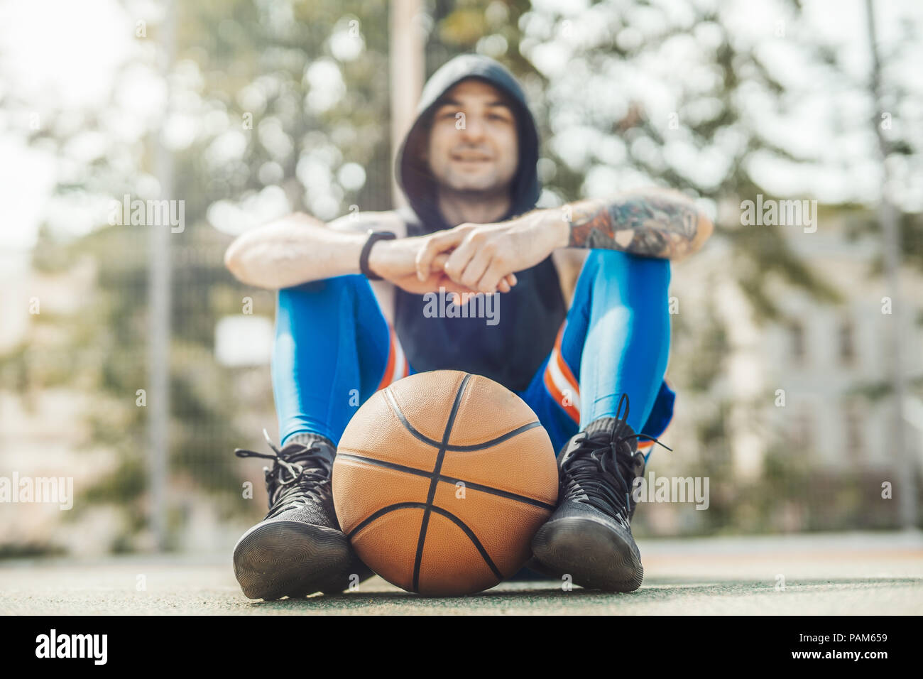 Bald attractive man sitting under basketball hoop and board on the basketball court. Man is on focus and foreground, background is blurred. - Stock Image