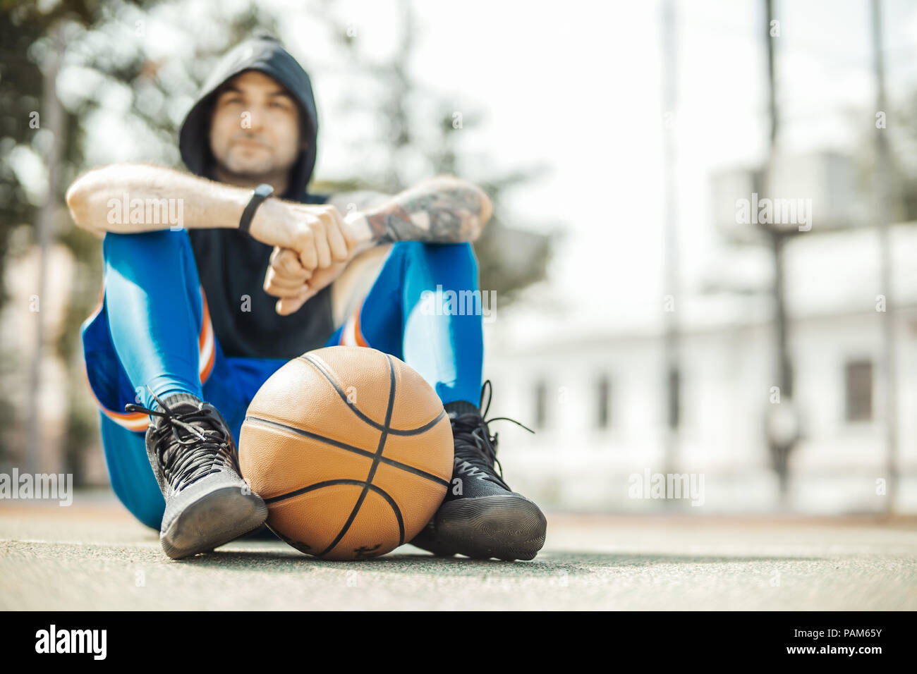 Close up of attractive man sitting on the court. Ball is on focus and foreground, man is on background and blurred. - Stock Image