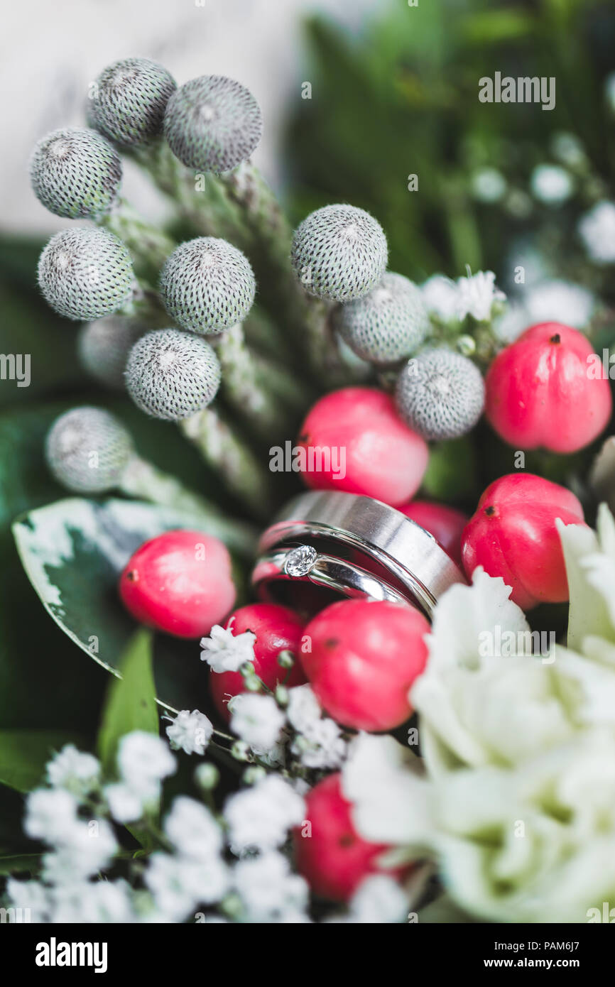 Two White Gold Wedding Rings In Casket Close Up With Fresh Flowers