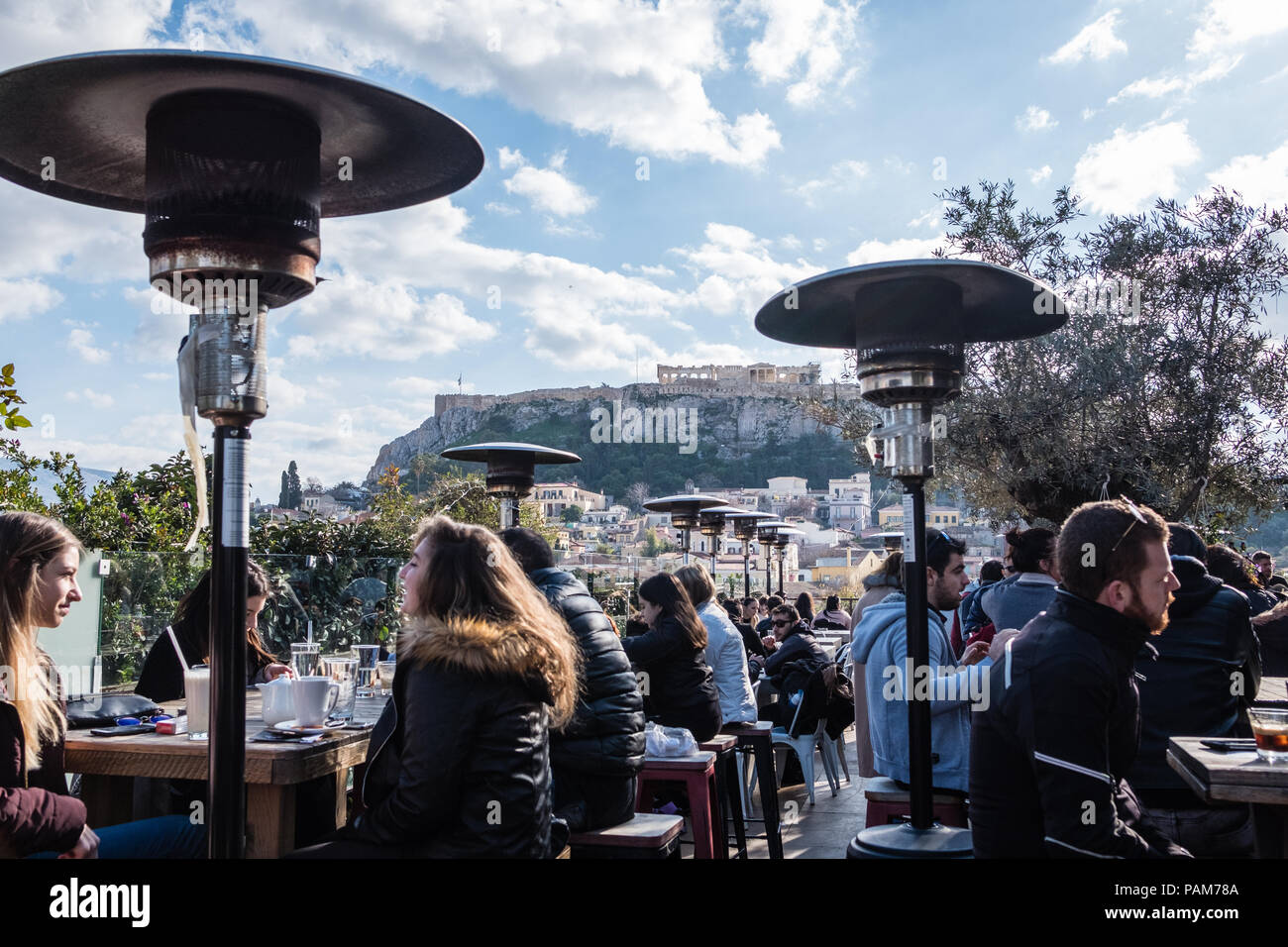 Young Athenians staying warm on a trendy rooftop city cafe with views of the Acropolis during winter, Athens, Greece, Europe. - Stock Image