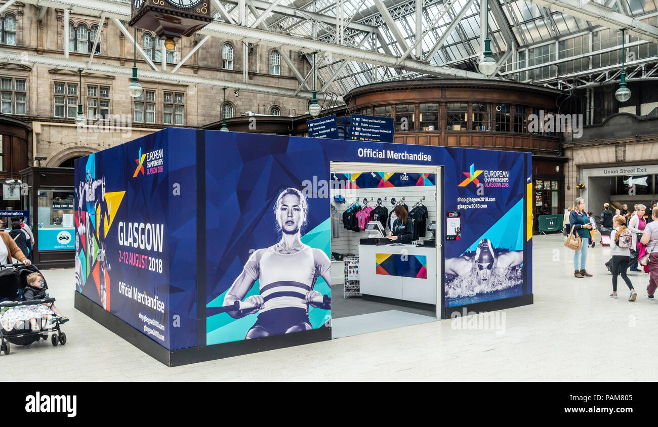 A Official Merchandise shop of Glasgow 2018, the multi-sport European Championships, at Glasgow Central Station covered with branding - Stock Image