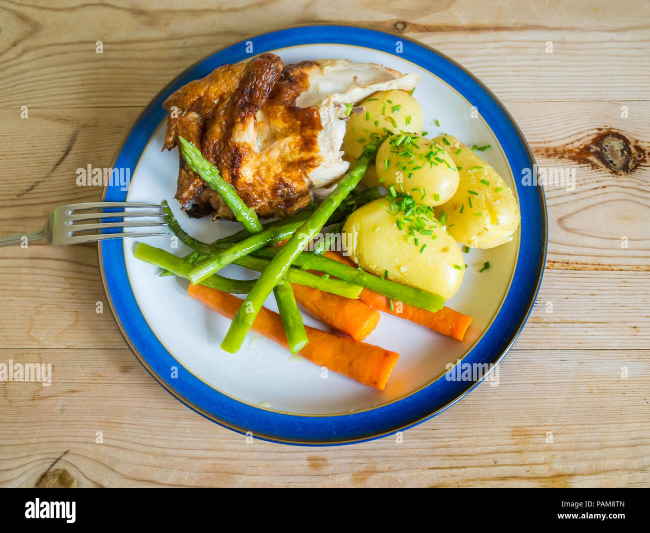 Lunch  a quarter roast chicken  with new potatoes carrots, green beans and chopped chives on a wooden table top Stock Photo