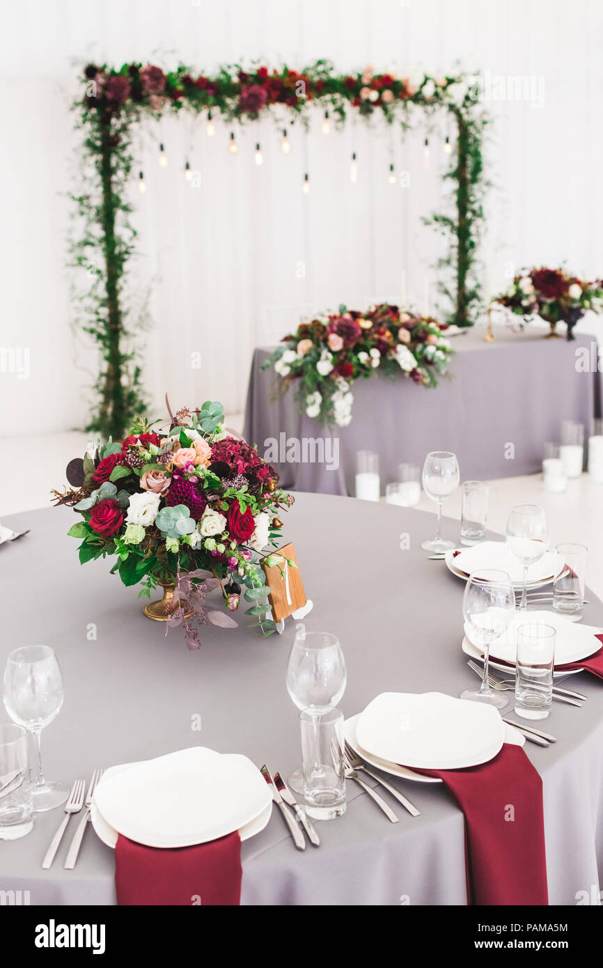 Wedding table, decorated with red flowers bouquets, candles, grey ...
