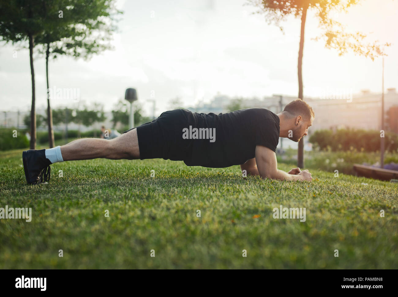 Distant plan of young attractive man exercising plank outdoors. Back view. - Stock Image