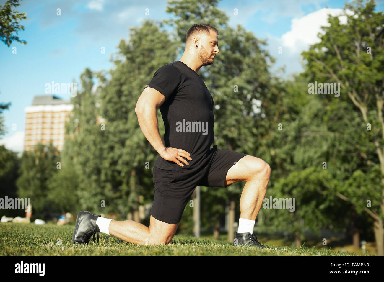 Young attractive man stretching legs outdoors doing forward lunge Man is on focus and foreground, background is blurred. - Stock Image